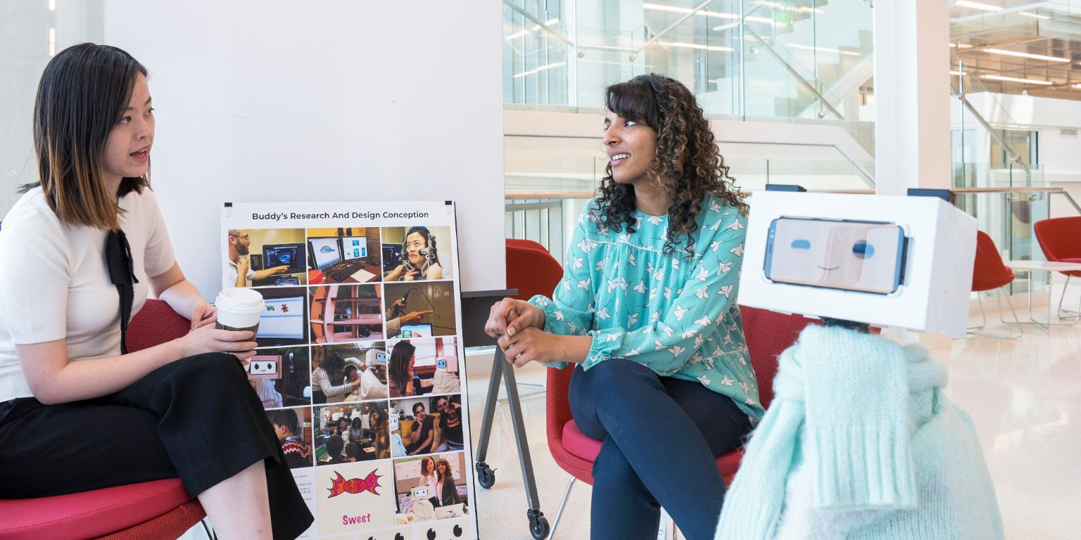 Tingyu Li, left, and Pavithra Ramamurthy sit with their speech therapy robot